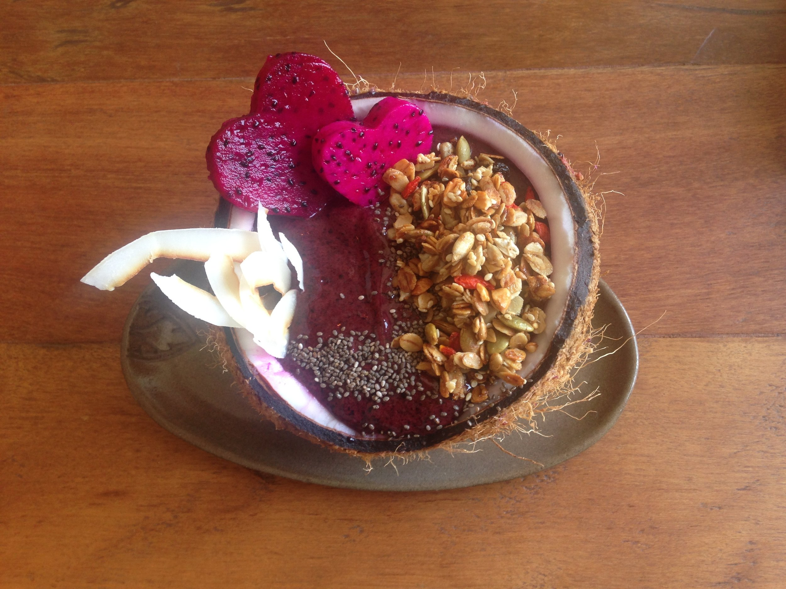 Granola and coconut shreds soaked in an acai bowl