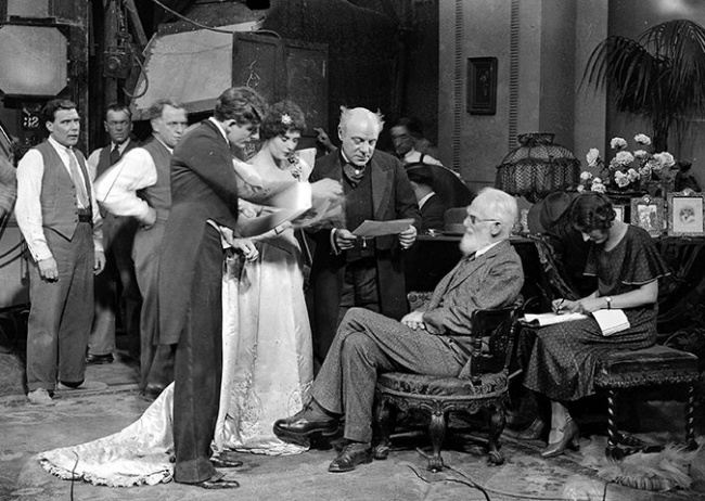 George Bernard Shaw, seated, speaks to actors on a visit to Elstree studios, where he watched the filming of his play How He Lied To Her Husband in October 1930.