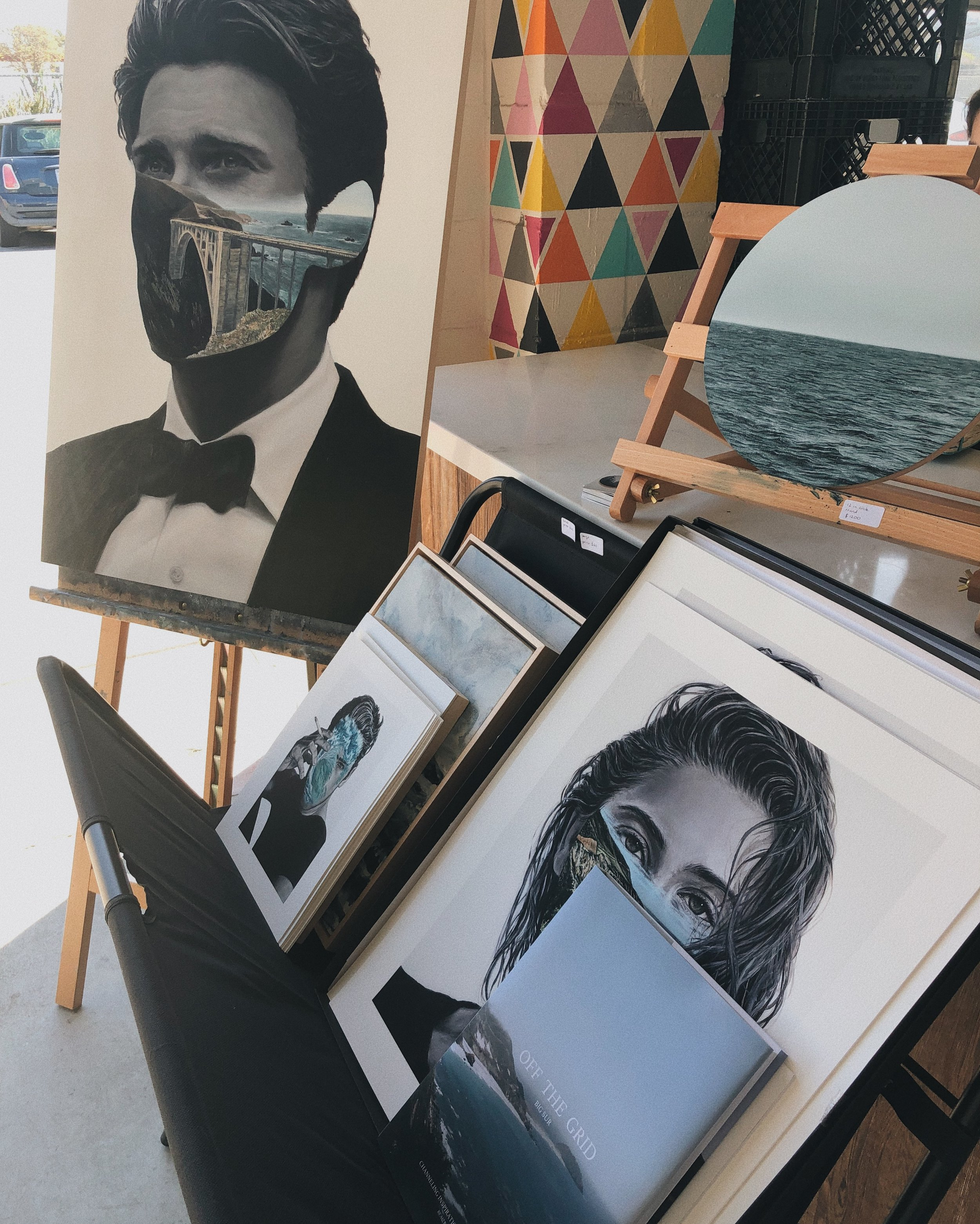 "Here I have some small prints ($25), large prints ($60), my Big Sur inspired book ""Off the Grid"" and some abstract ocean paintings with ""Mr. Bixby"" and a circle window piece."