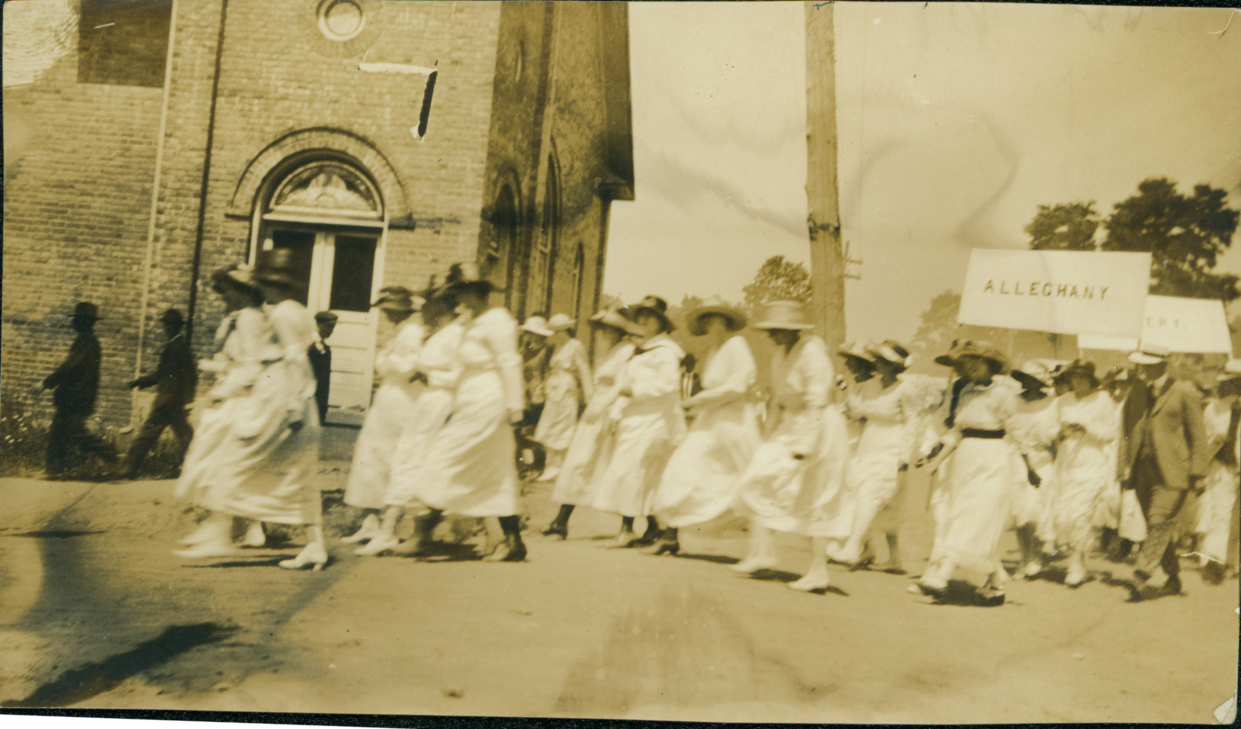 """Women marching in the July 4, 1919, parade through Boone turn right from West King St. (then known as """"Main Street"""") onto today's College Street in front of the First Baptist Church (built 1916, demolished 1936). Image courtesy of the H. L. and Gladys Coffey Collection, Digital Watauga Project."""
