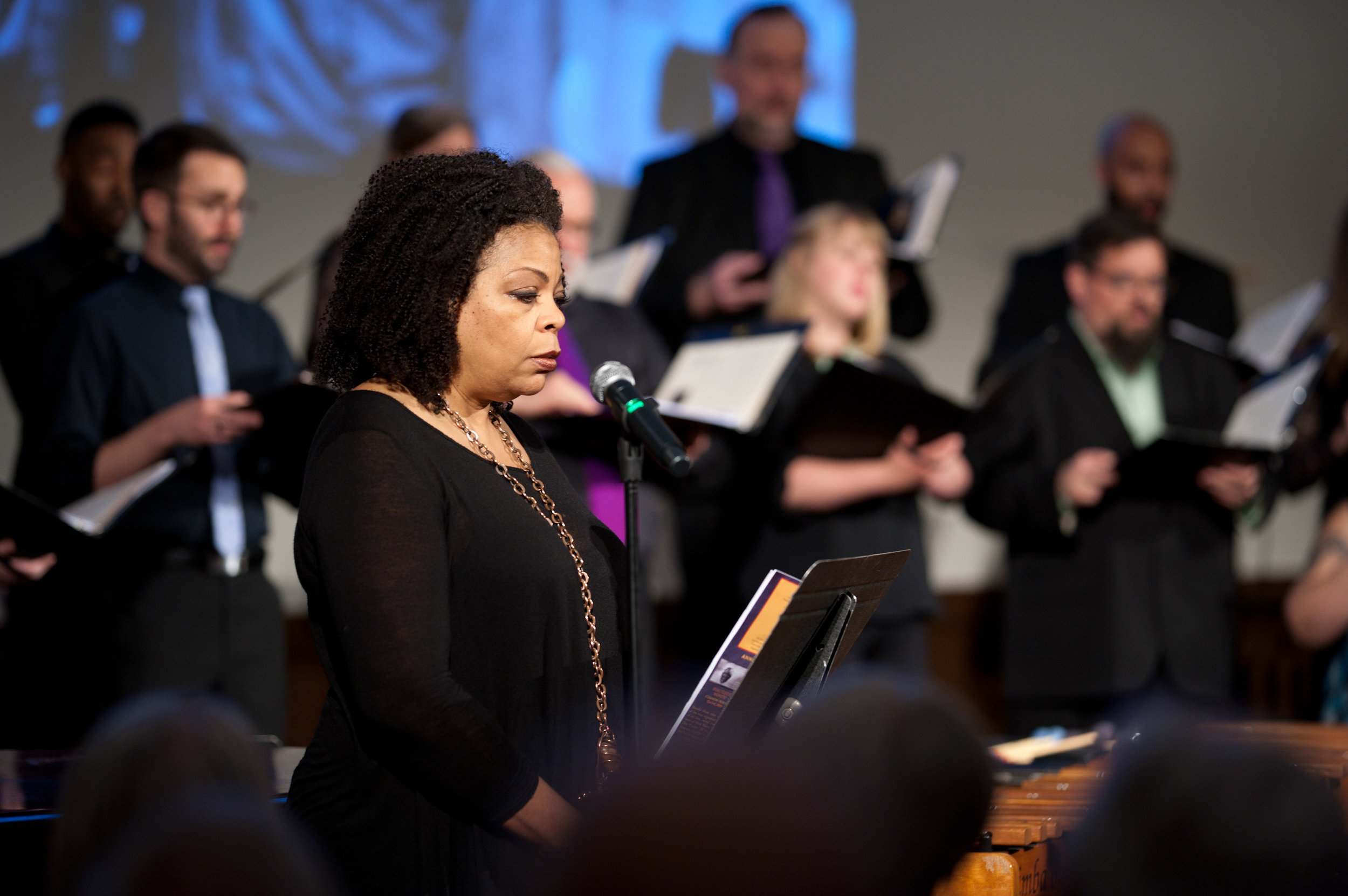 Poet in Residence S. Renee Mitchell performs with the choir for the world premiere of Damien Geter's piece  The Talk: Instructions for Black Children When They Interact with the Police. (Photo Credit: Rachel Hadiashar)