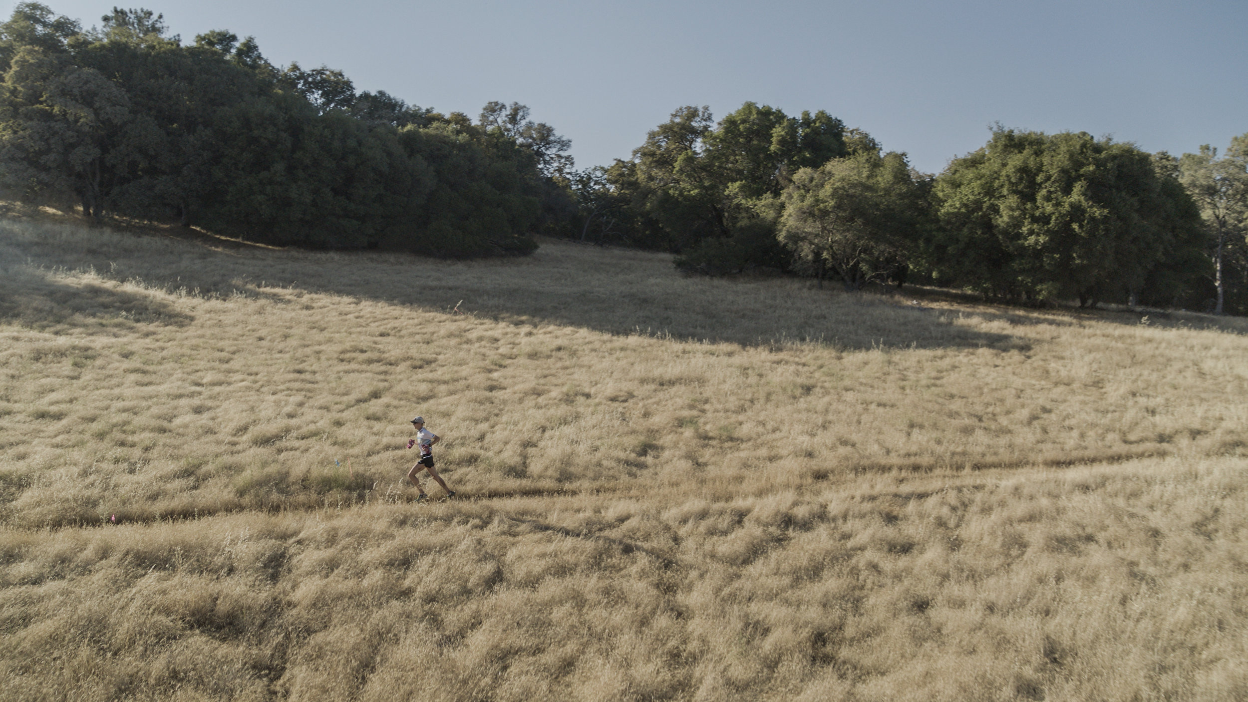 The race leader Jim Walmsley cruises into an aid station at Pointed Rocks at mile 94. Near Auburn, California.