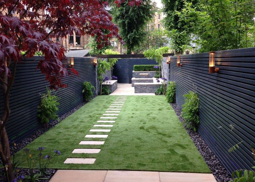 Long narrow contemporary garden in Glasgow's West End with gunmetal grey contemporary fencing - this one has lighting behind it that shines out from the spaces at night