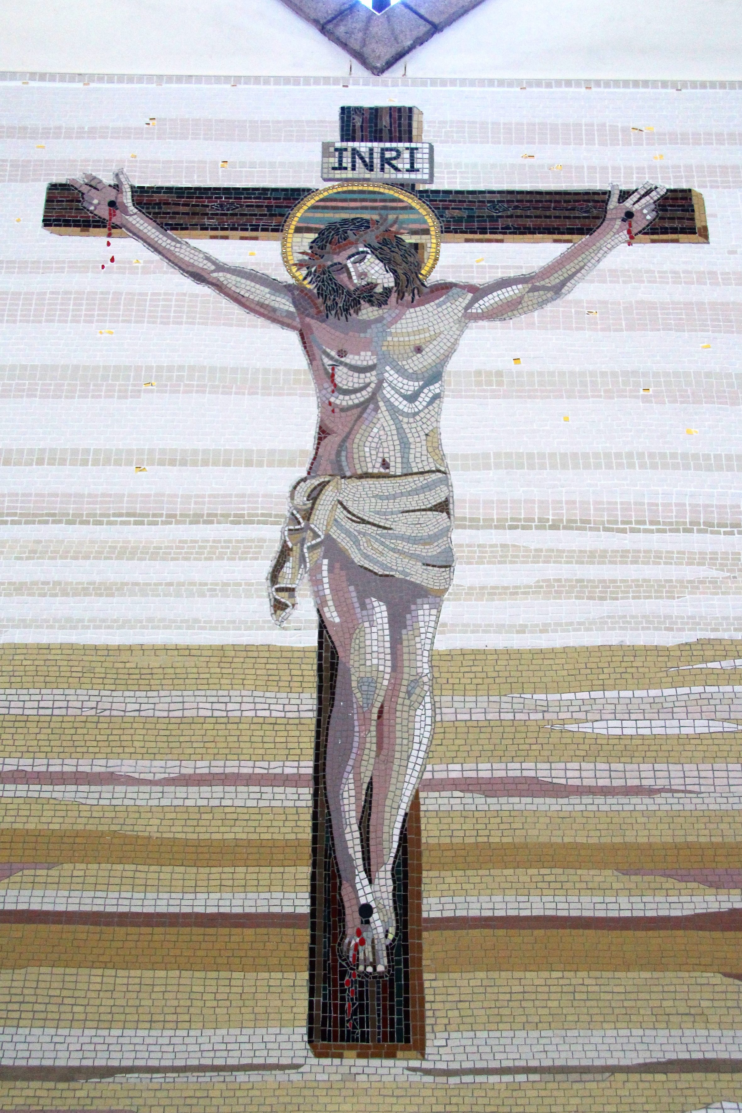 Mosaic of the Crucifixion at Our Lady of the Rosary Catholic Church, Buckley, North Wales. Matt porcelain tile, smalti on fibreglass mesh, cement fixed in situ onto block wall. Approximately 10ft. x 8ft.