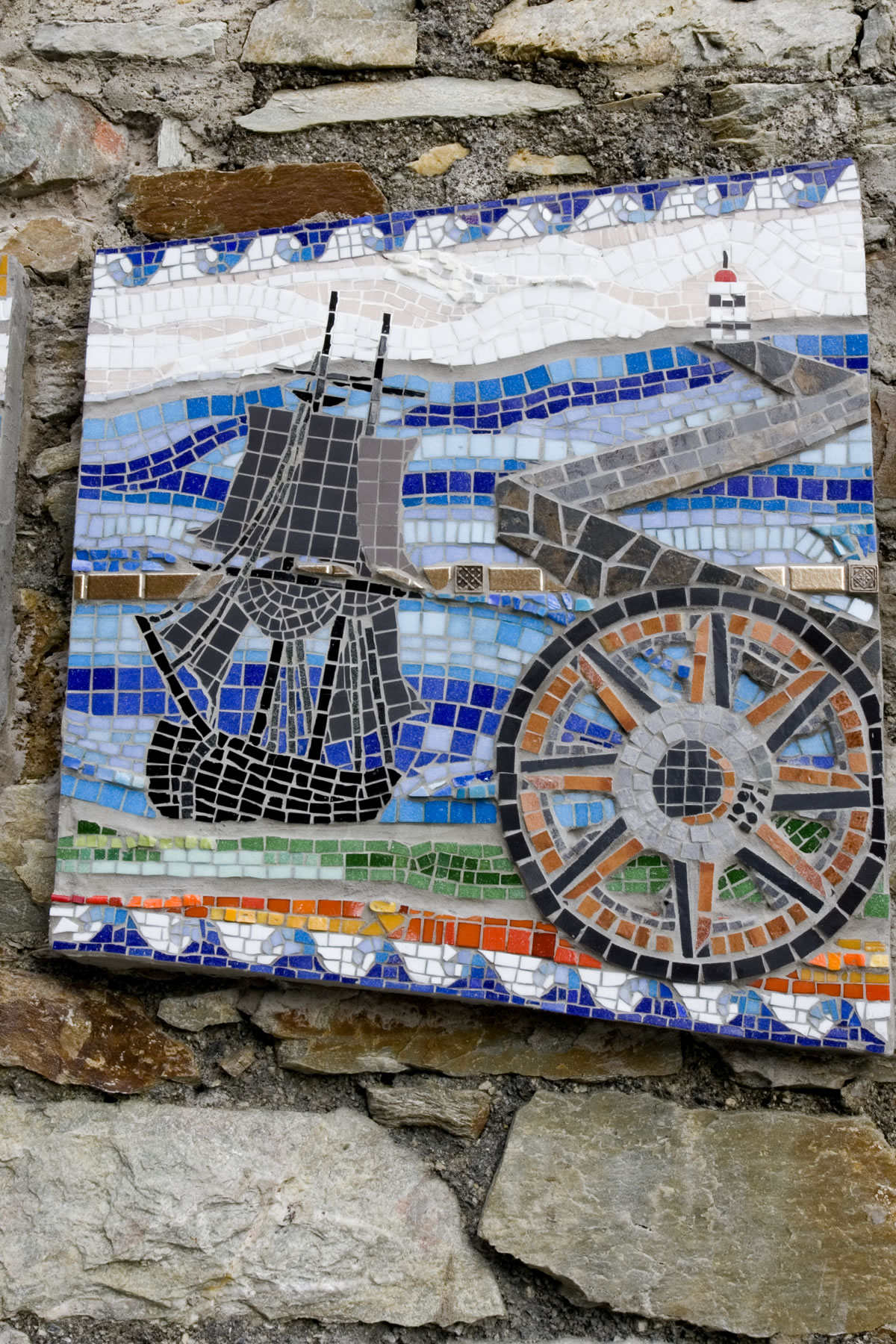 Timeline - p  anel 3. Depicting the maritime history and industry, Holyhead breakwater and lighthouse.   Elements of air, water and fire stream through the design along a bronze timeline. Border of tidal waves.