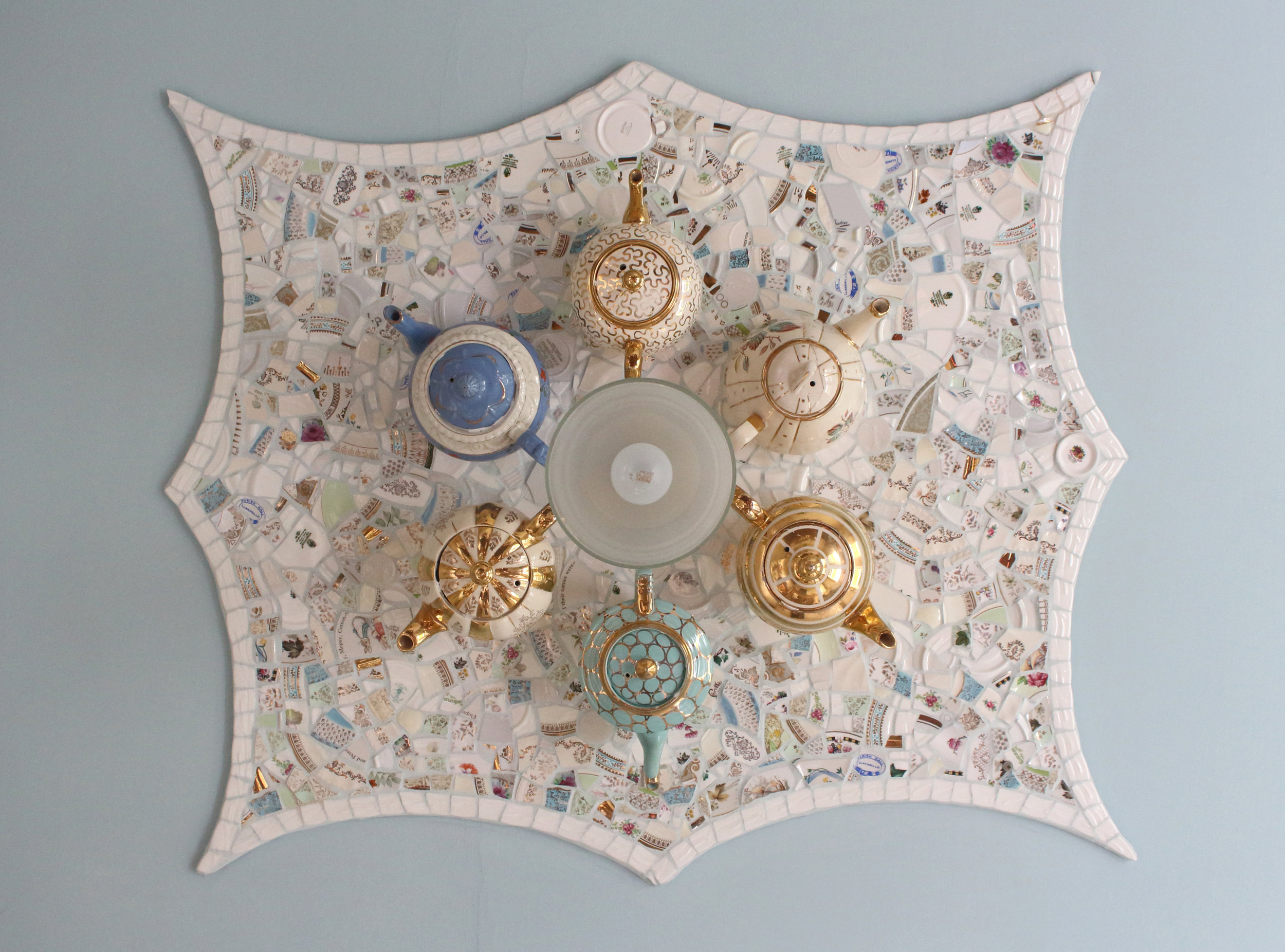 Antique teapot ceiling mosaic. This mosaic was built using recycled antique china and porcelain teapots fixed upside down onto the ceiling with a recycled china plate background ceiling rose and central light fixing. I was reminded of my love of the story of Alice in Wonderland as a little girl.  Approx. 45ins. x 36 ins.