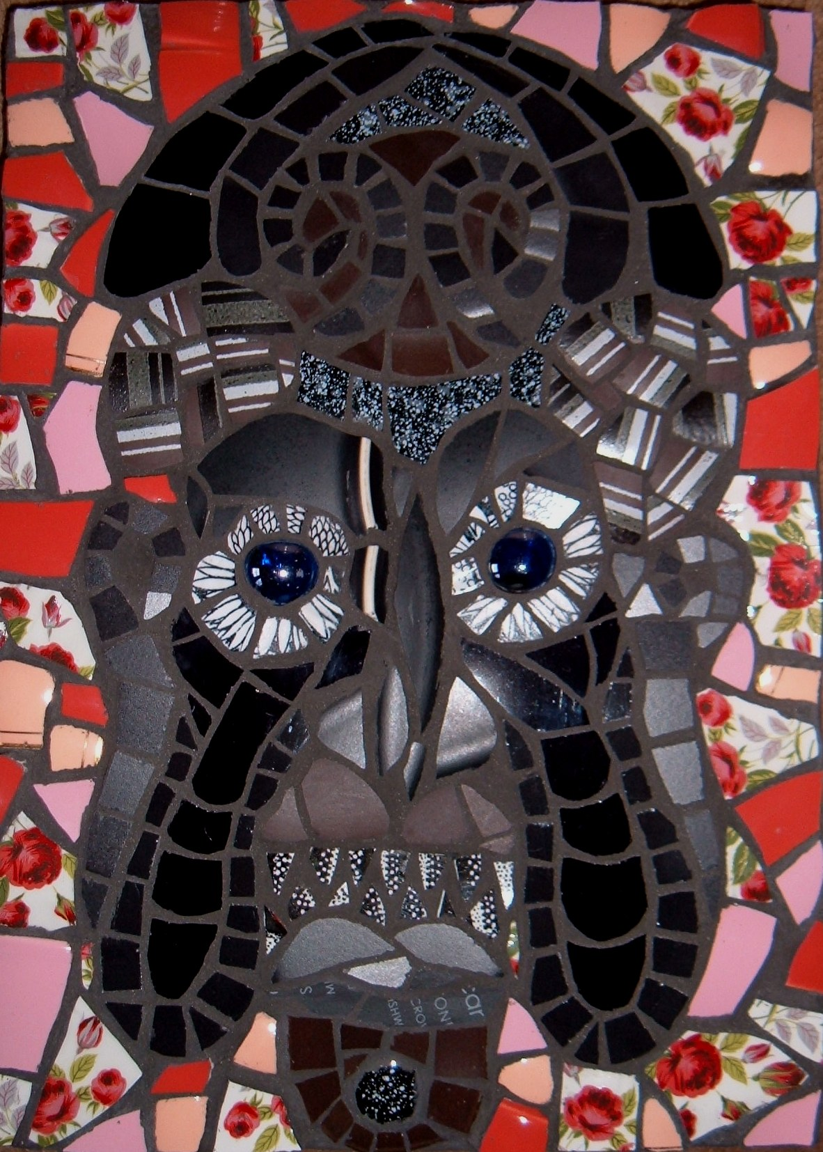 "Grim Mask. Inspiration for this mosaic came from an ancient oak door carved with ""Comedy and Tragedy"" theatrical masks. The door is to be found at Plas Newydd (www.llangollen.com/ gallery/1.jpg), the home of the Ladies of Llangollen in North Wales. Recycled china and porcelain, ceramic,glass beads.  Approx. 12 ins. x 9ins"