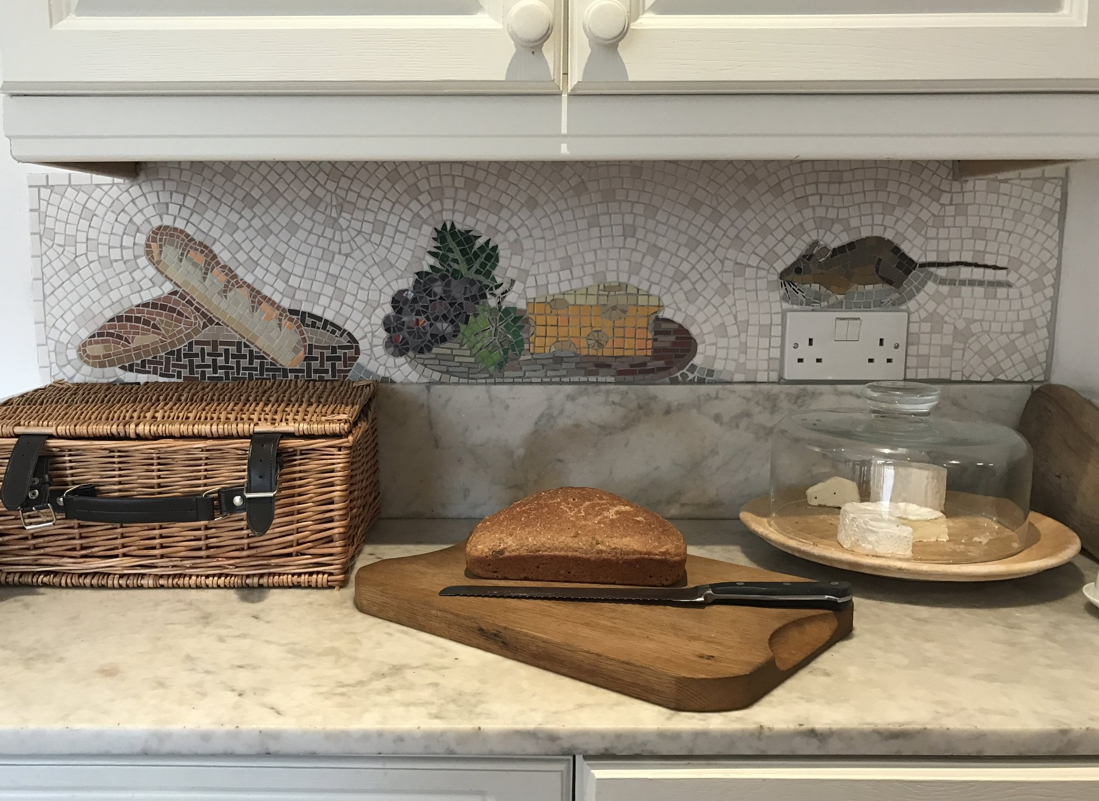Splashback for a marble worktop. Basket of bread, grapes and cheese board and MOUSE. Matt porcelain, recycled crockery, vitreous glass. 12ins. x 48ins