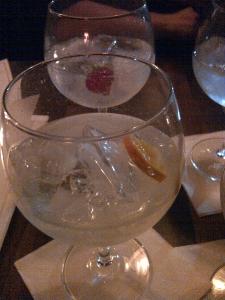 Gin with a strawberry garnish and gin with an orange garnish