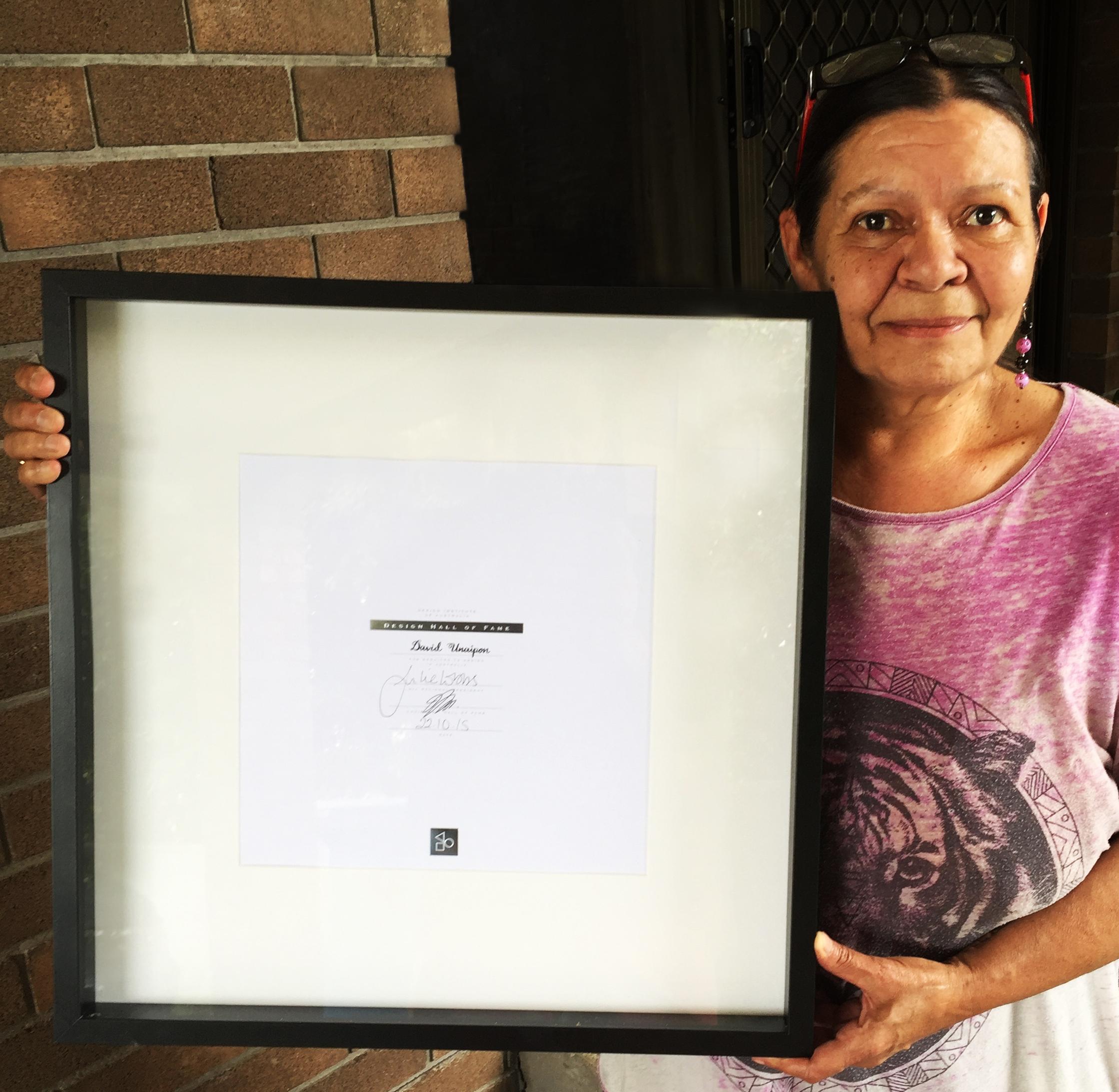 Elaine Kropinyeri holding her uncle David's Design Hall of Fame certificate.