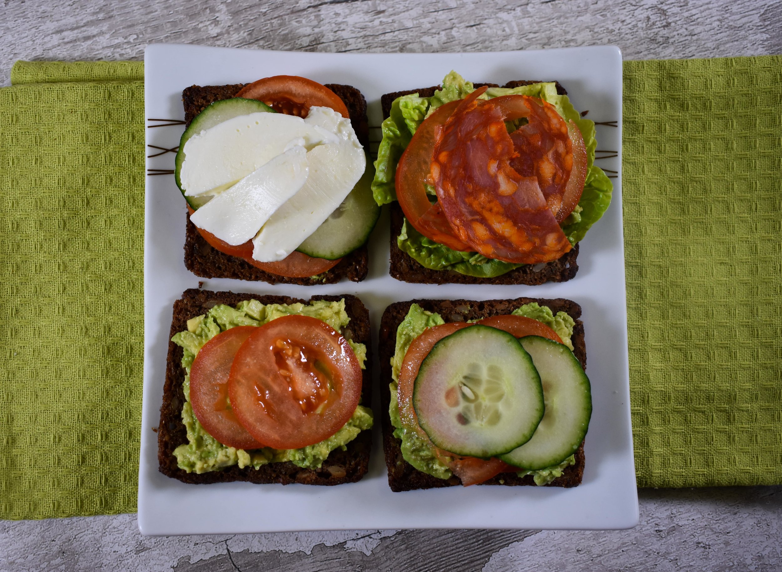 Our German Rye Bread open sandwiches with a mixture of avocado, tomato, cucumber, lettuce, mozzarella and salami