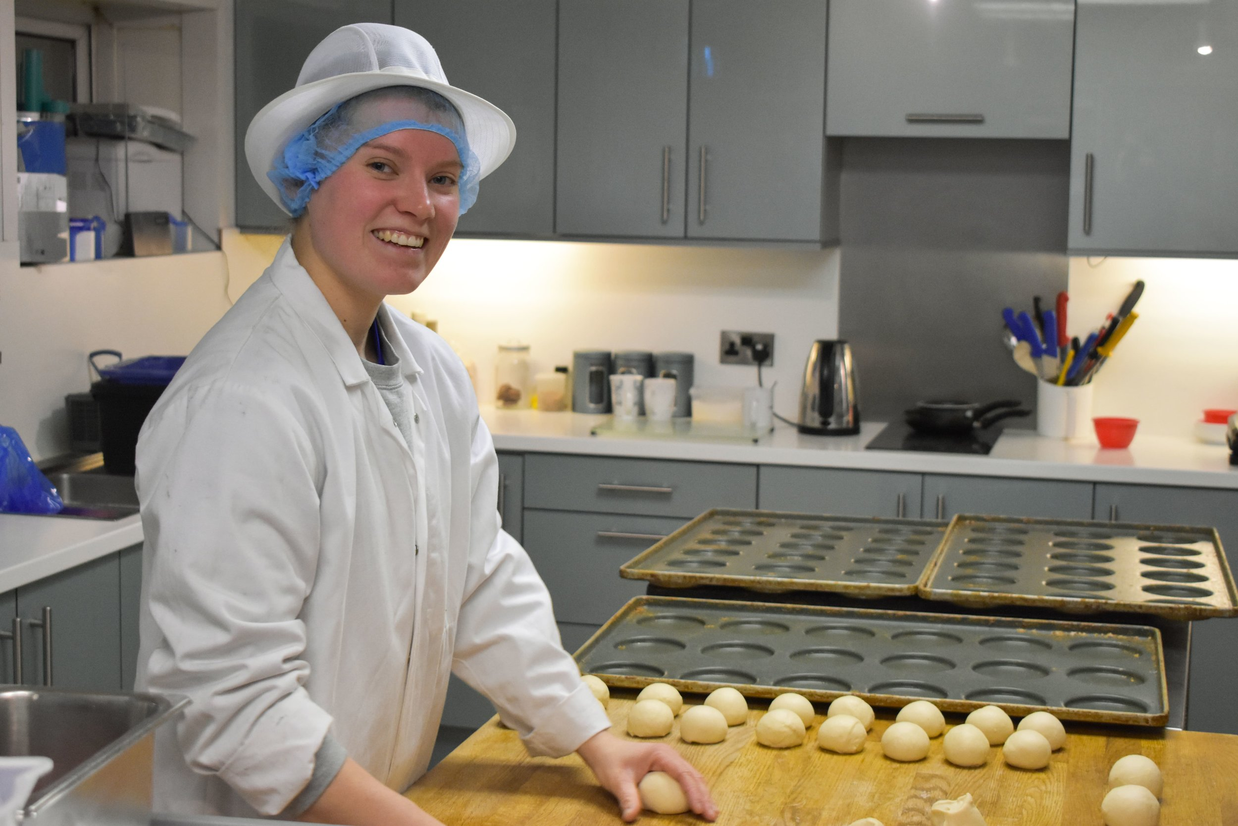 KATY ROBINSON - I have been at Fosters Bakery for around 5 months now as I started mid-November. After going to University and studying a Hospitality with Culinary Arts Degree, I knew I wanted to pursue my interest in food. I began in foodservice but my real interest was in product development. When I came to Fosters for my interview, I was mesmerised by the bakery and all the machinery and different types of bread they produced. After that, I knew it was the place I wanted to work.On a standard day, we receive requests off of customers who are asking for a specific product. My colleague Adam then creates or alters a recipe to fit the brief, this can involve making alterations to ingredients such as sugar, salt, whether they want it palm or soya free. My job involves weighing up ingredients for the samples ready to make the next morning. This can range from mini box loaves, brioche, bloomers, breakfast muffins to hot dog rolls.My role is very varied and I love that we are doing something different each day. Additionally, we may have requests from customers who want something tweaking in a product which they already take. For example, a customer has just requested a 'cleaner' brioche which contains no e-numbers or soya. Other aspects of my role involve trial and error, not necessarily requested by a customer but our ideas which we put to the sales team. For example, I made some white rolls with added Christmas themed chutneys in last week to see if they could work for a special Christmas roll!