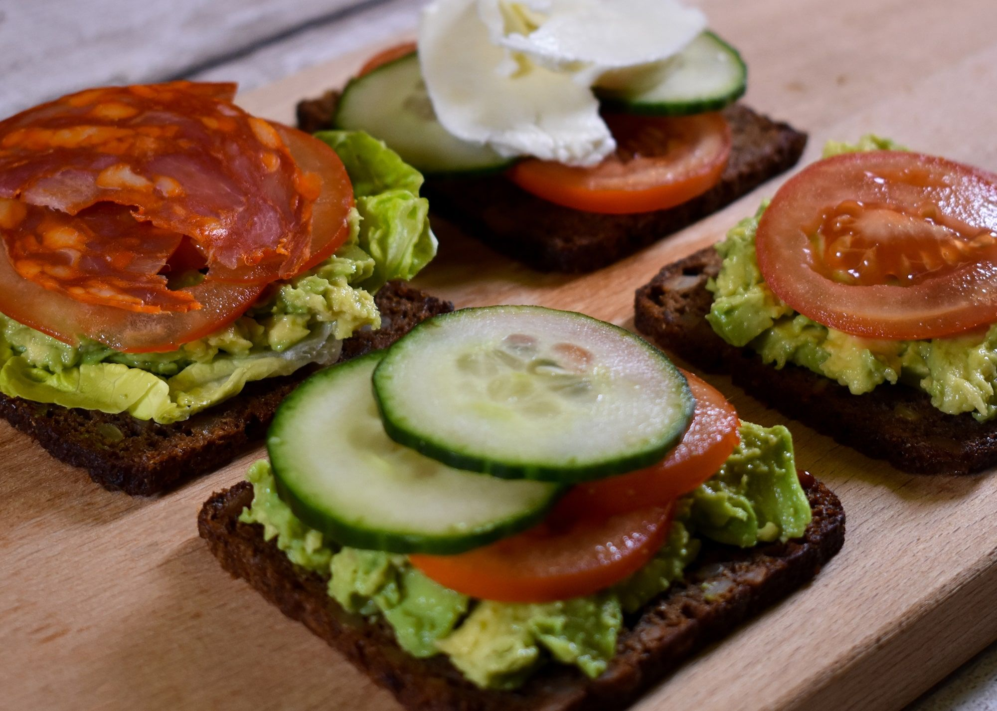 Open sandwich with German rye bread with a mixture of toppings, including avocado, tomato, cucumber, salami and mozzarella