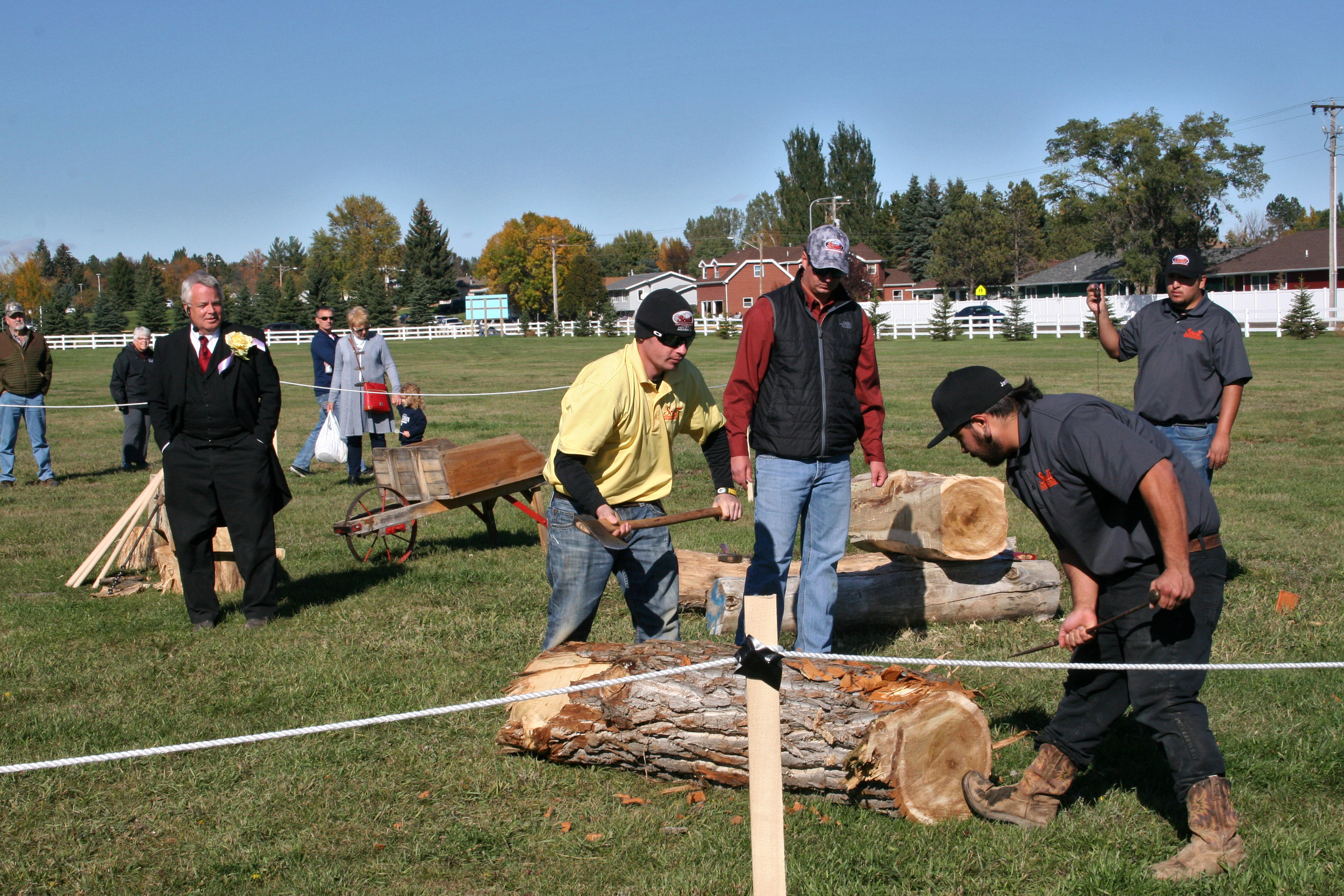 Scull Construction workers debark a cottonwood log as Theodore Roosevelt, portrayed by Clay Jenkinson, looks on.