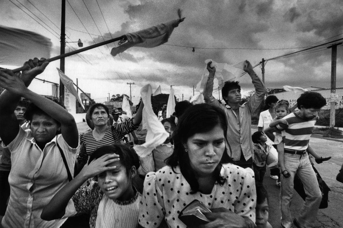 In November 1989, civilians in a zone held by insurgents flee their working-class barrio after three days of aerial bombing by the Salvadoran air force in Soyapango, El Salvador. Photo by Donna DeCesare.