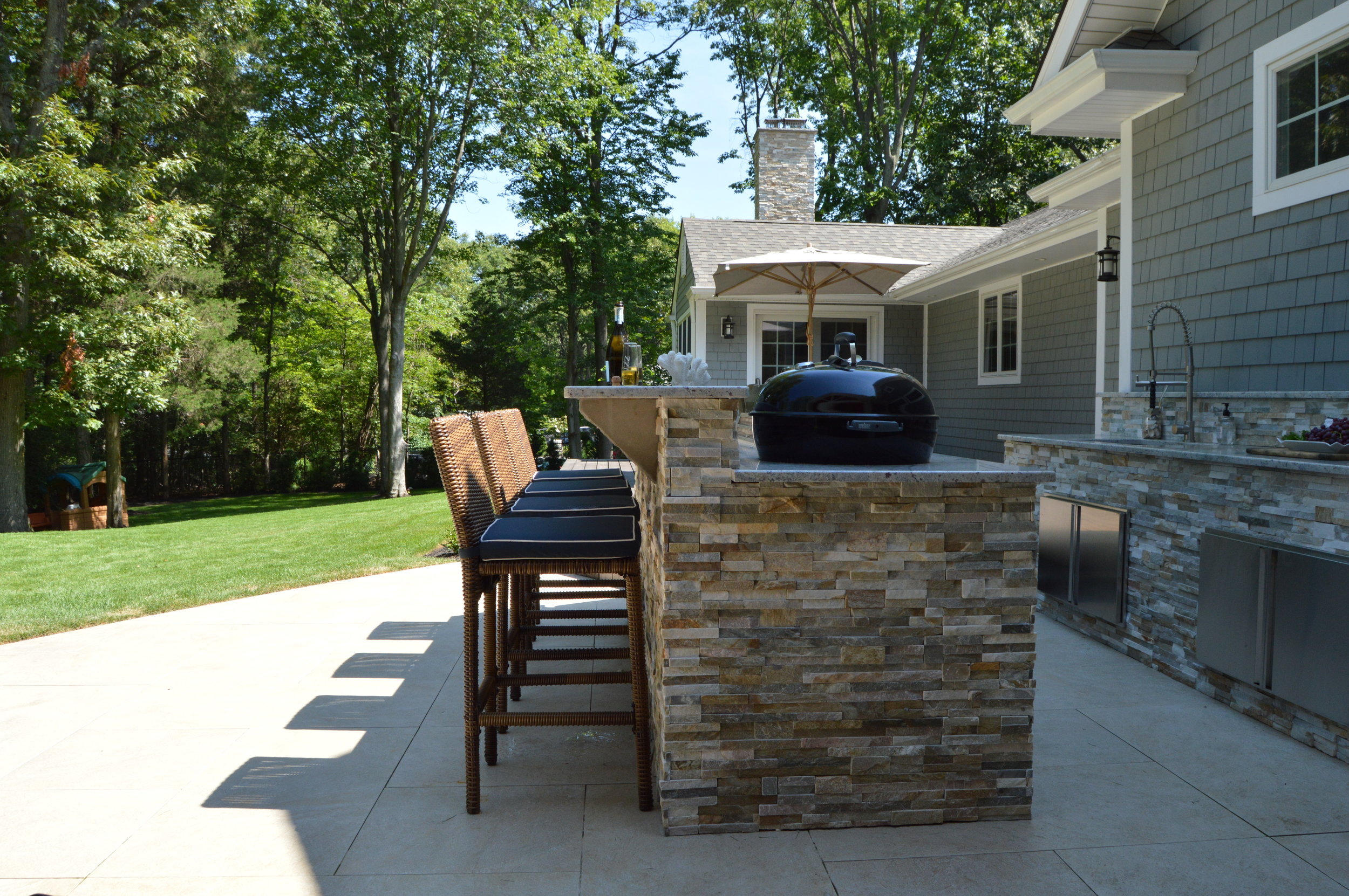 Long Island outdoor kitchen and bar with seating and natural stone