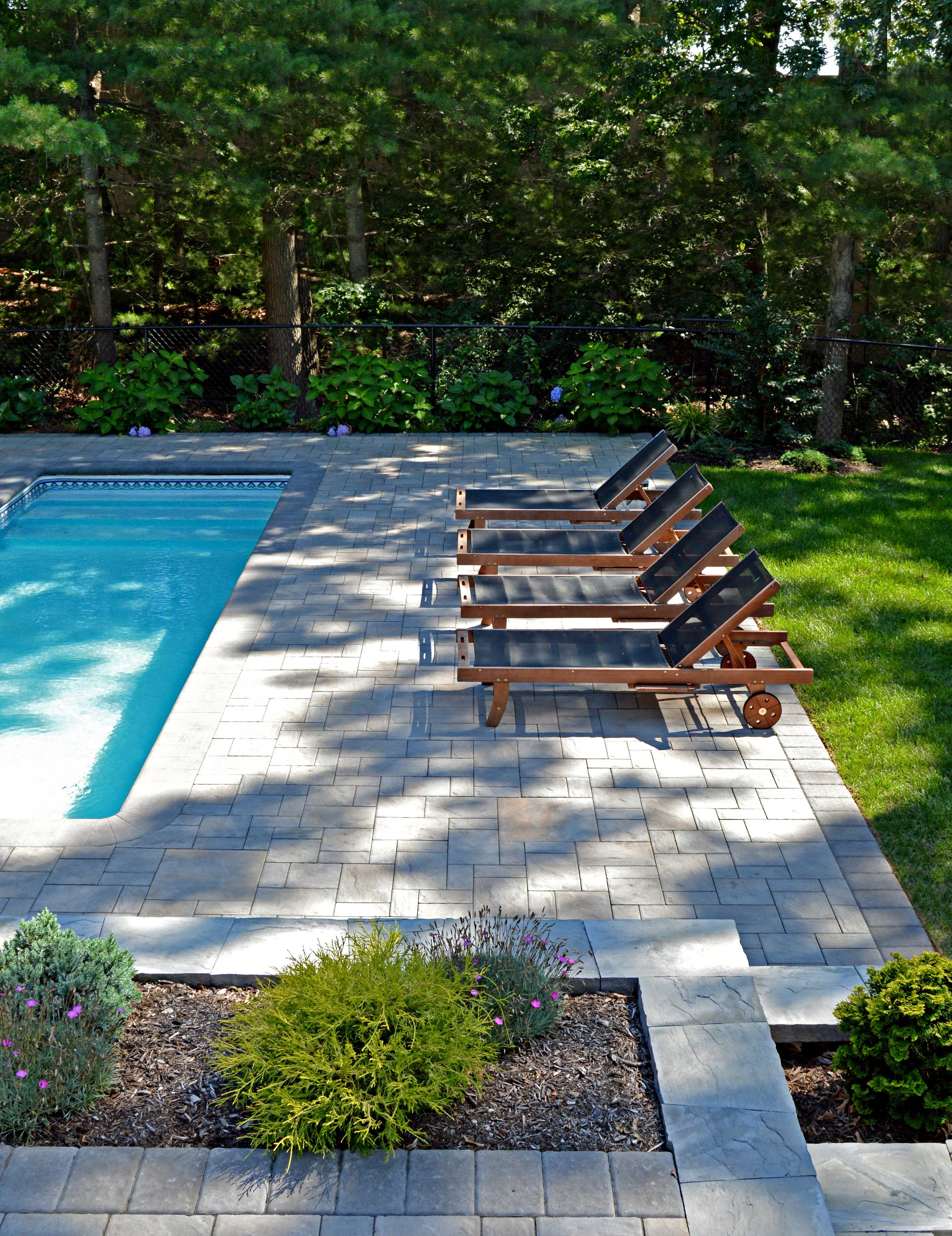 Long Island patio by a pool with lounge chairs in Bethpage, NY