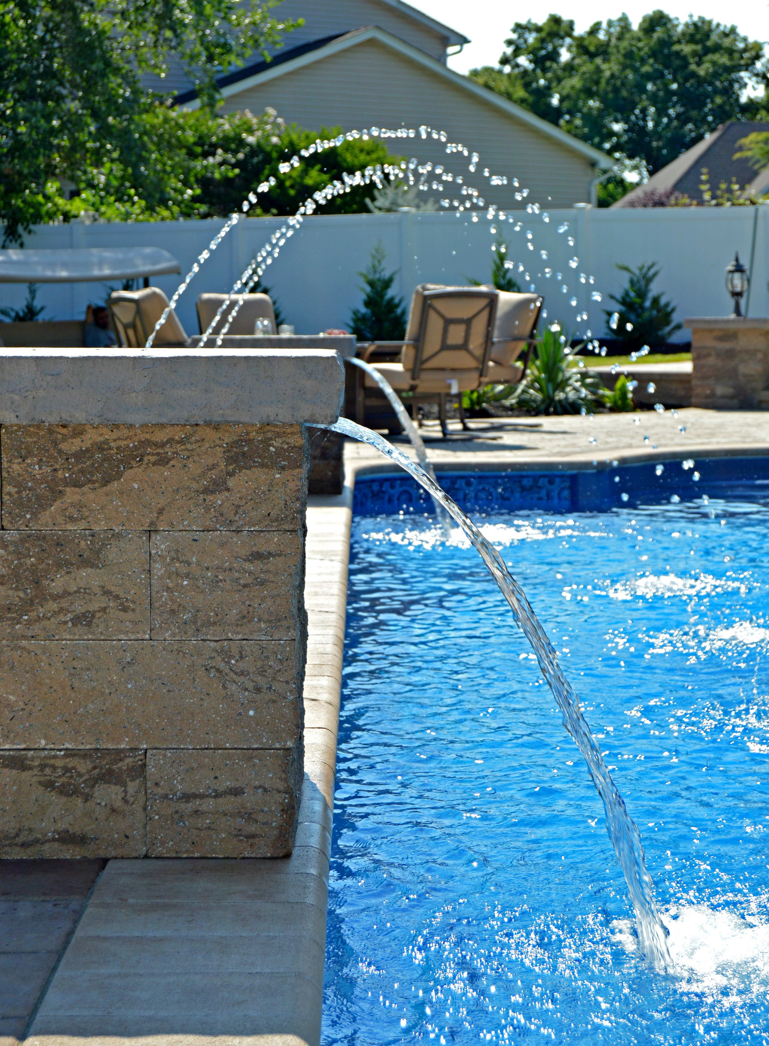 unilock paver patio and swimming pool with water fountain in Bohemia, NY