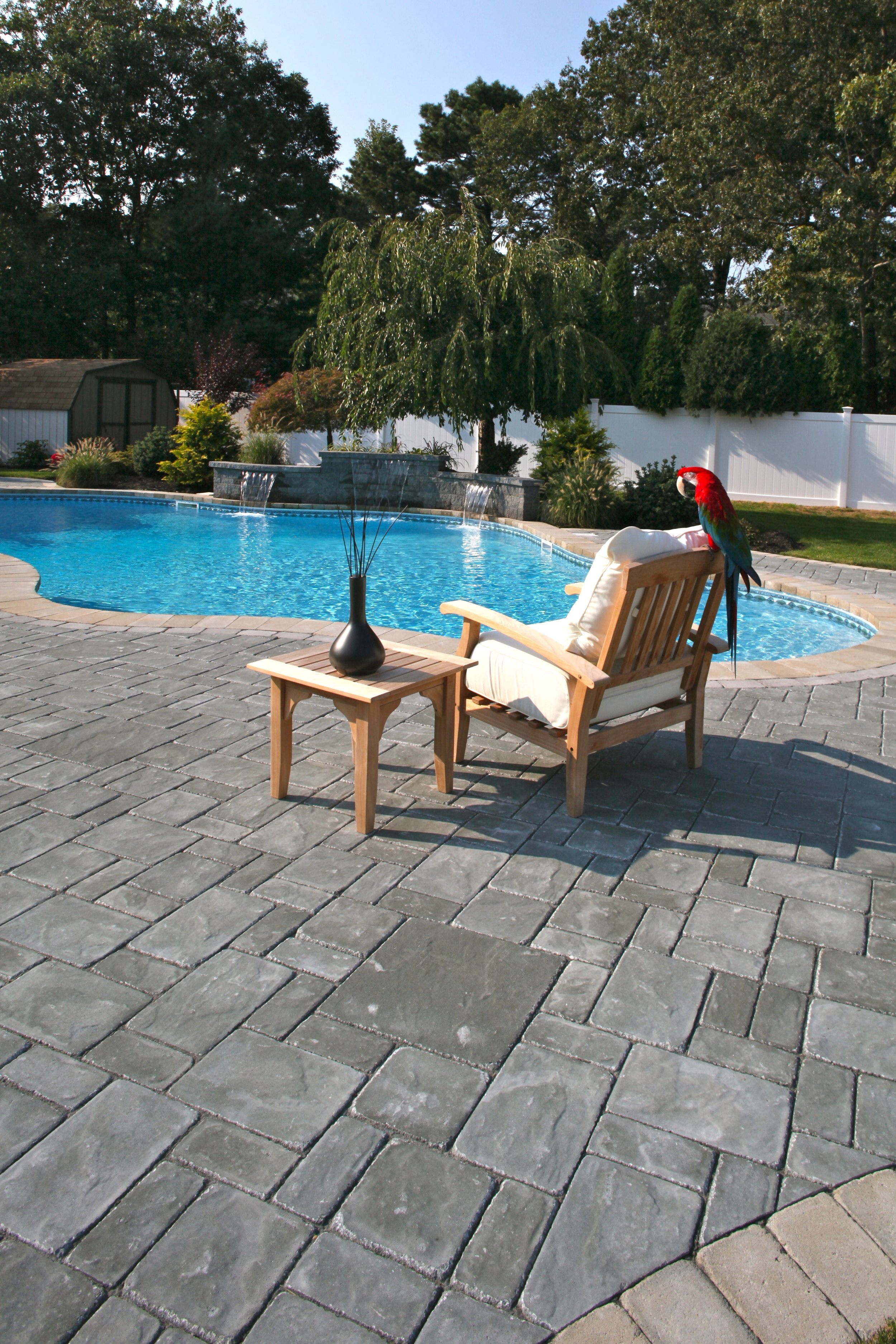 relaxing by a freeform swimming pool design and walk up patio in Long Island, NY