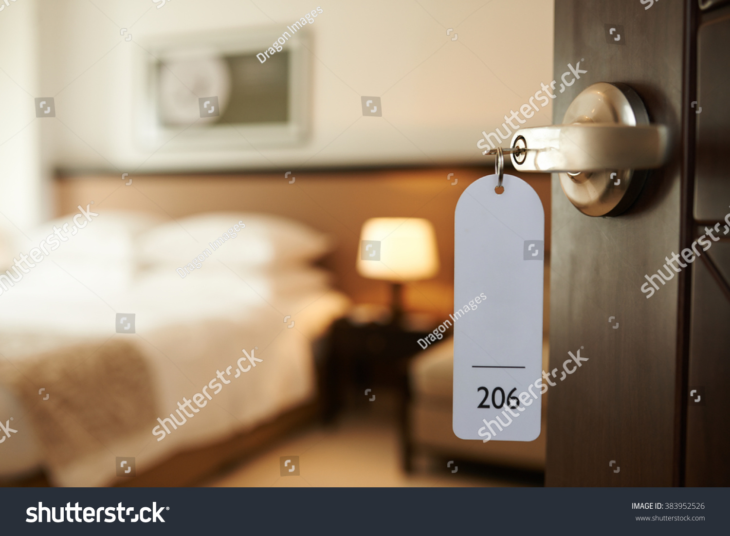 stock-photo-opened-door-of-hotel-room-with-key-in-the-lock-383952526.jpg