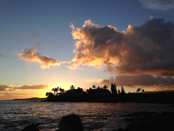 """Sunset at """"The Wall"""", a gathering place in Koloa, Hawaii, where locals and tourists come together to watch sunsets over the water."""