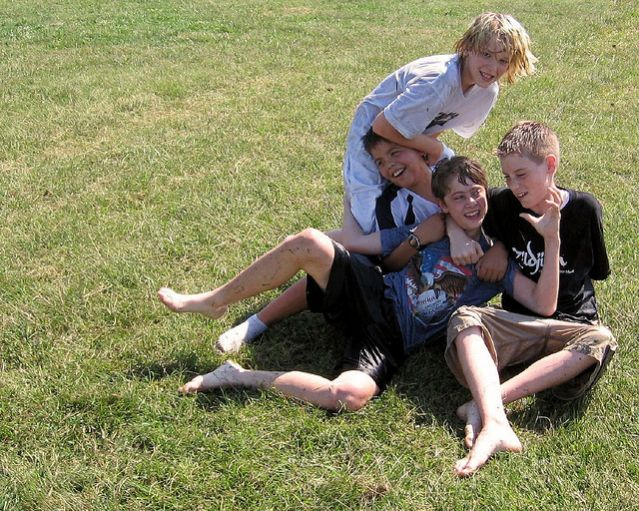Notice everyone's smiles. Even the boy on the bottom, who looks like is getting tackled by the boy in the white.