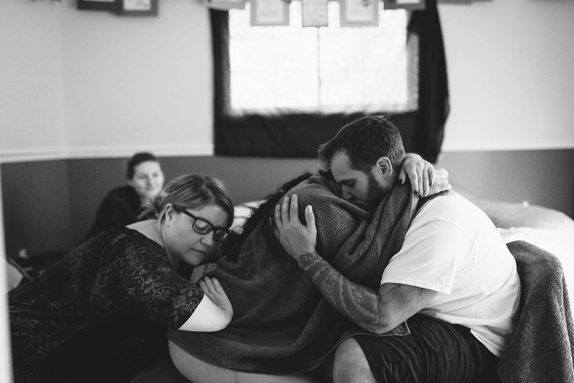 In questo parto in casa, la ostetrica preme sulla schiena della mamma per aiutarla a superare una contrazione (onda). Photo credit:  Lauren Allmond Photography