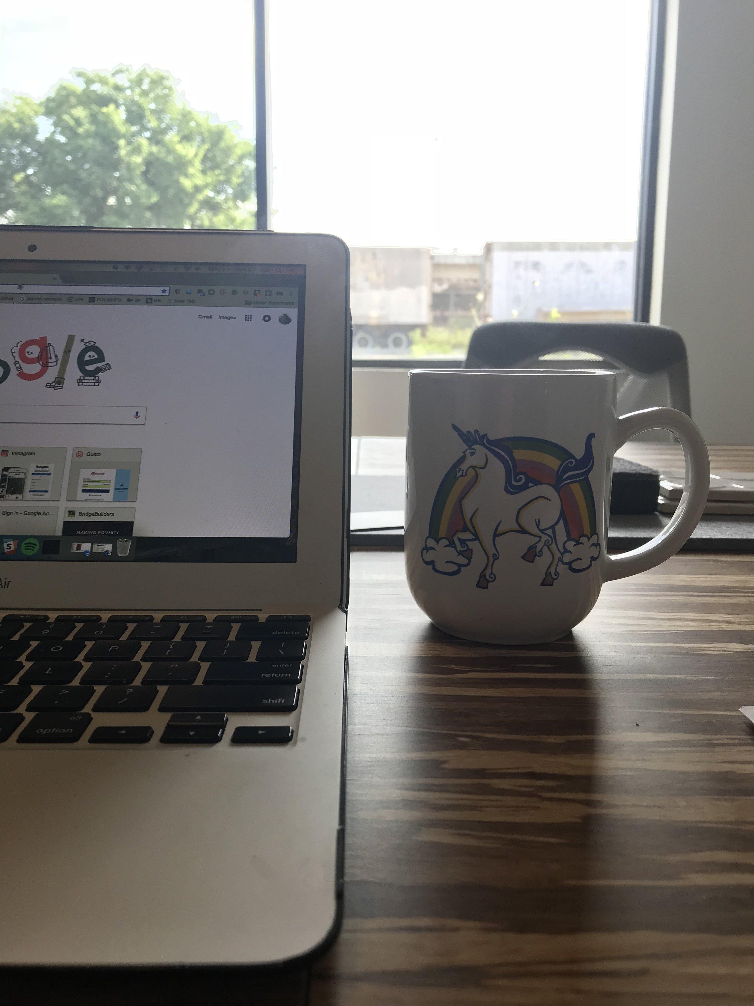 Sunshine, unlimited coffee, and a unicorn mug makes our Development Director, Sarah Conner, one happy BridgeBuilder.