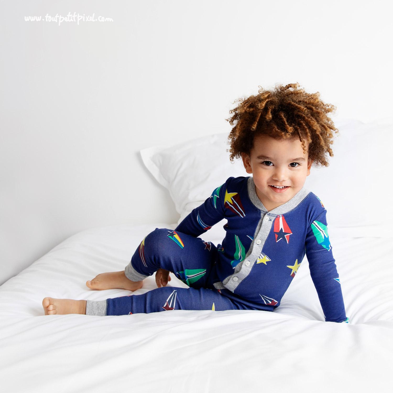 Portrait d'un enfant de 3 ans souriant sur le lit en pyjama par Tout Petit Pixel, photographe enfant Marseille