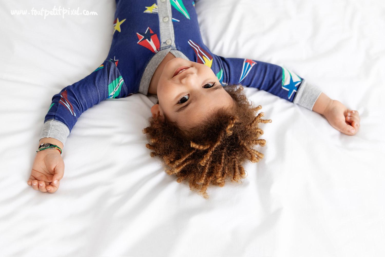 Jeune enfant à coupe afro qui sourit allongé sur un lit par Tout Petit Pixel, photographe enfant Marseille
