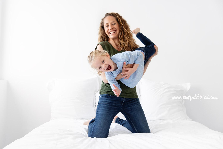 Mère et fille qui jouent sur le lit en riant par Tout Petit Pixel, photographe enfant et famille à Marseille