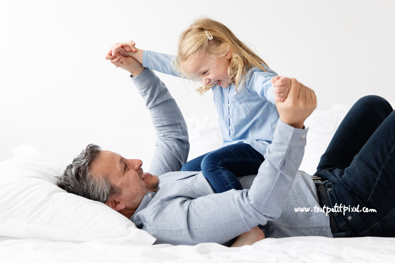 Petite fille et son papa qui jouent sur le lit en riant par Tout Petit Pixel, photographe enfant et famille à Marseille