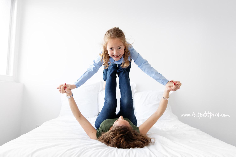 Petite fille qui tient en équilibre sur les pieds de sa maman par Tout Petit Pixel, photographe enfant et famille à Marseille