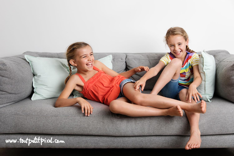 Deux petites filles qui rient sur un canapé par Tout Petit Pixel, photographe enfants lifestyle