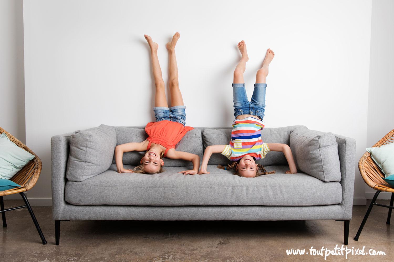 Enfants qui font le poirier sur un canapé par Tout Petit Pixel, photographe enfants lifestyle à Marseille