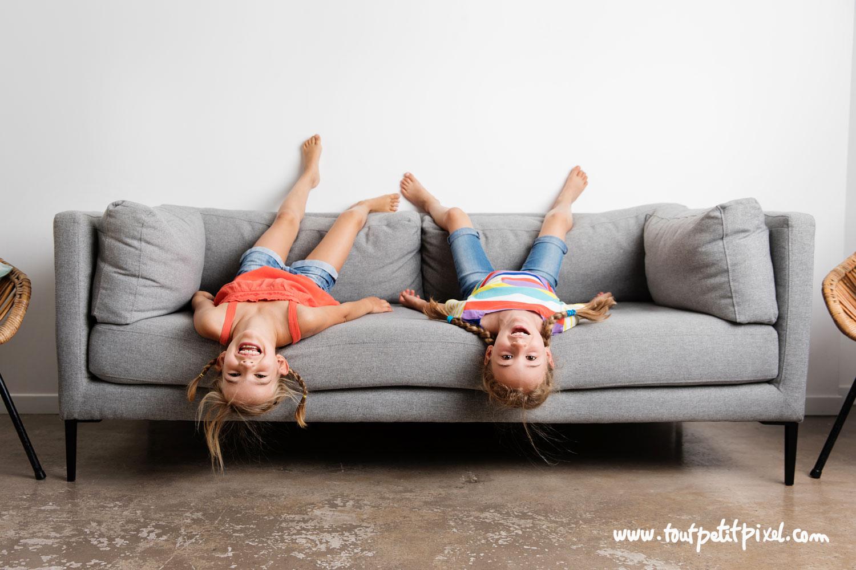 Petites filles à l'envers sur un canapé par Tout Petit Pixel, photographe enfants Marseille