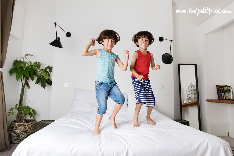 Frères jumeaux qui sautent sur un lit par Tout Petit Pixel, photographe enfant lifestyle à Marseille