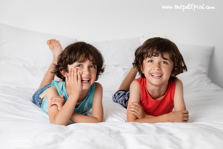 Deux jumeaux qui sourient sur un lit par Tout Petit Pixel, photographe enfants lifestyle à Marseille