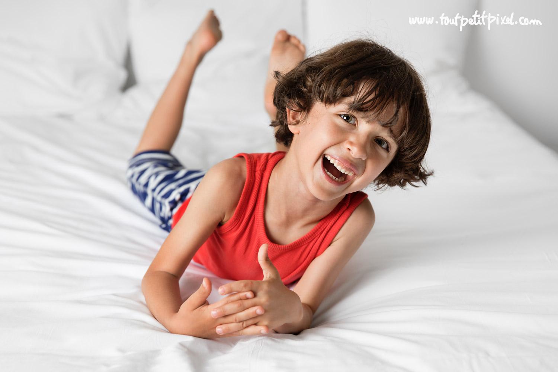 enfant qui rigole sur un lit blanc par Tout Petit Pixel, photographe enfant lifestyle à Marseille