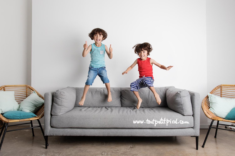 Frères jumeaux qui sautent sur un canapé par Tout Petit Pixel, photographe enfant lifestyle à Marseille