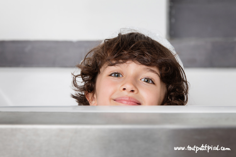 Enfant qui sourit en prenant son bain par Tout Petit Pixel, photographe enfant lifestyle à Marseille