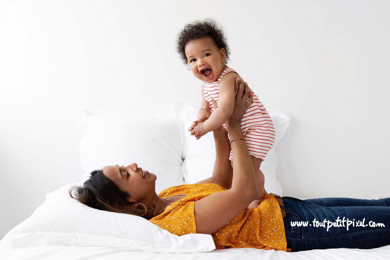 Maman et bébé souriant qui jouent sur un lit par Tout Petit Pixel, photographe enfant Marseille