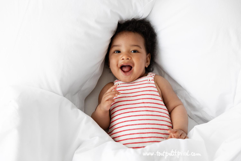 Bébé de 7 mois qui sourit sur un lit blanc par Tout Petit Pixel, photographe enfant Marseille