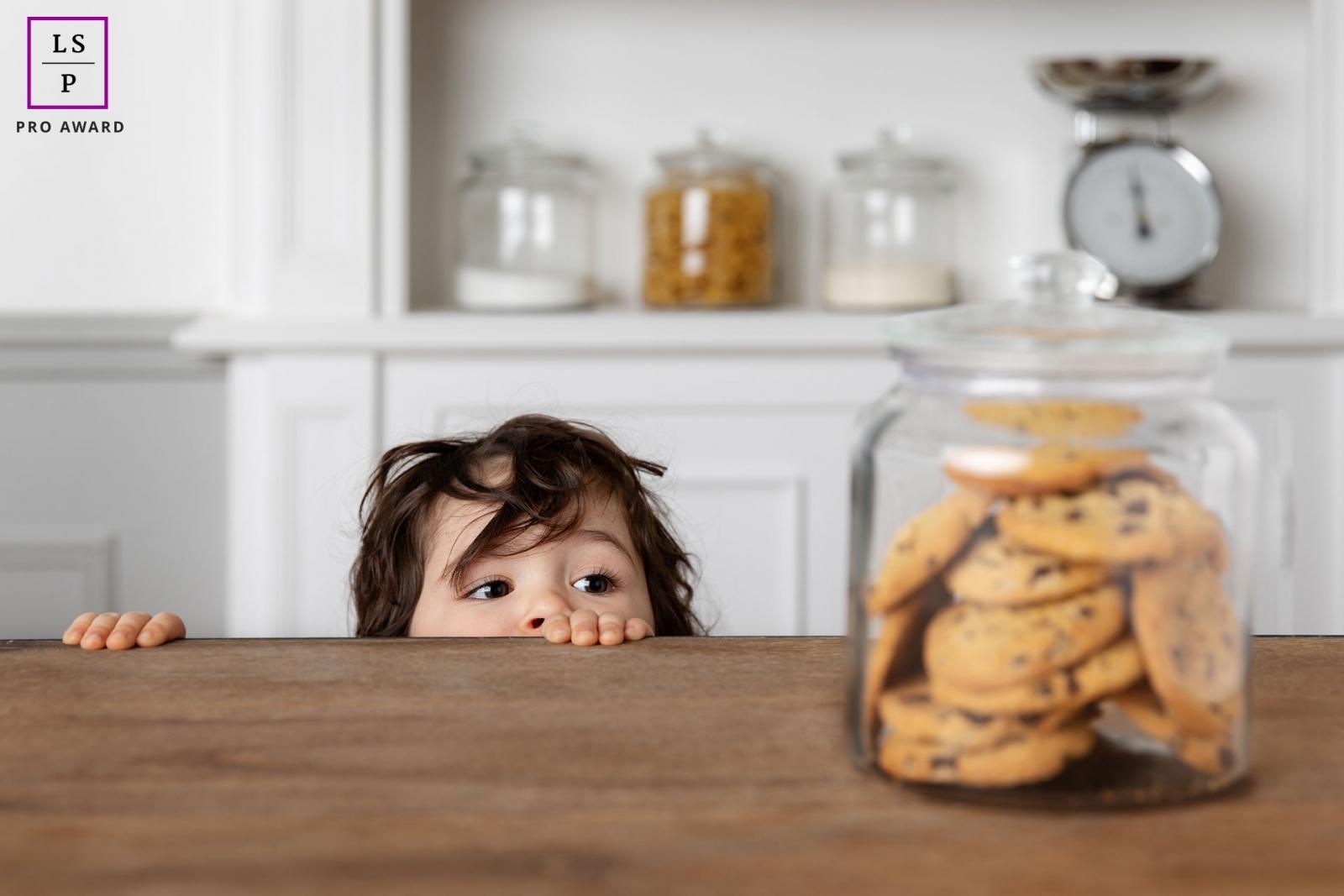 Jeune enfant qui essaye d'attraper des cookies sur la table par Tout Petit Pixel, photographe enfant lifestyle