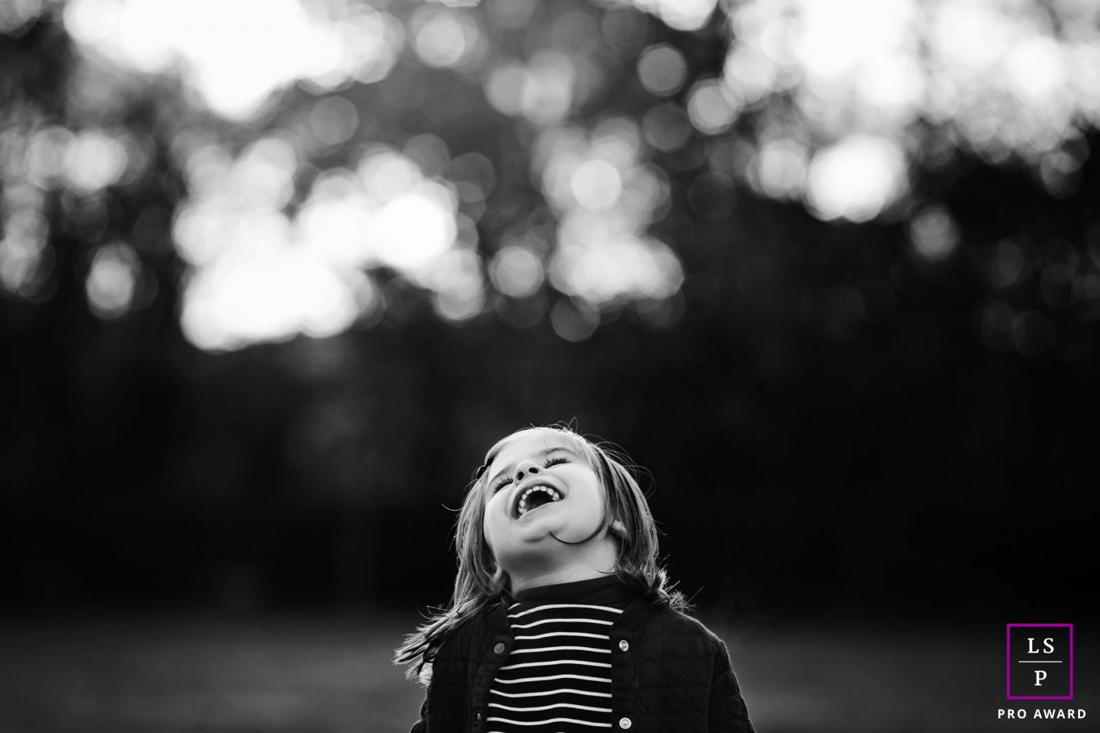 Portrait noir et blanc d'une petite fille qui rit par Tout Petit Pixel, photographe enfant lifestyle
