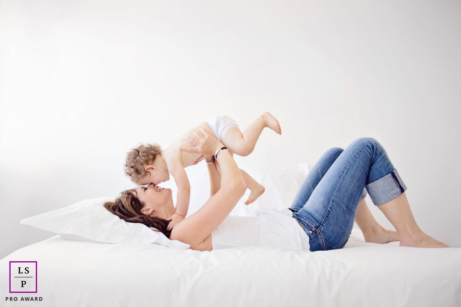 Maman et son bébé qui jouent sur le lit en riant par Tout Petit Pixel, photographe enfant lifestyle