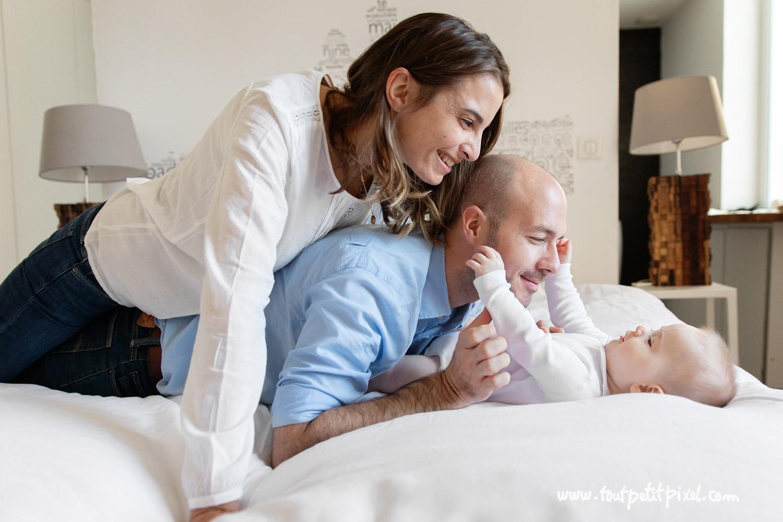 Parents et bébé qui jouent sur un lit par Tout Petit Pixel, photographe bebe lifestyle à Marseille