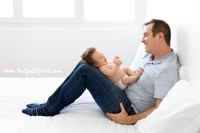 Papa et bébé de 2 mois qui rient ensemble face à face par Tout Petit Pixel photographe naissance Marseille