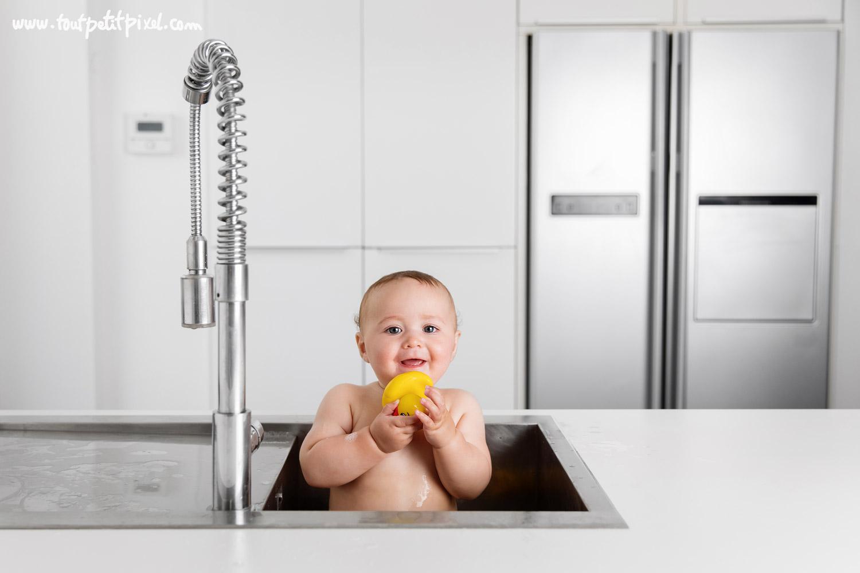 bébé souriant qui prend un bain dans l'évier par Tout Petit Pixel, photographe enfant lifestyle