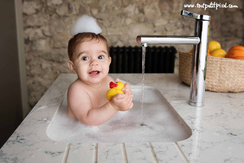 bébé qui prend un bain dans l'évier en jouant avec un canard de bain par Tout Petit Pixel, photographe enfant lifestyle
